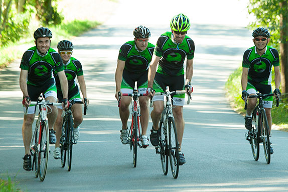 Group of bicyclists in matching green uniforms